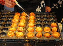 Bolas de torneado del pulpo del takoyaki del cocinero en la parrilla, Osaka, Japón Imagen de archivo