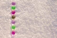 Bolas de vidro coloridas do Natal no fundo de brilho da neve fotos de stock royalty free