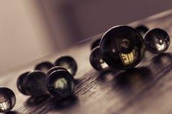 Bolas de vidro em uma superfície de madeira em um ângulo Trabalho artístico à moda Foco seletivo foto de stock royalty free
