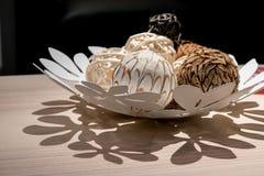 Bolas decorativas de la armadura de madera en el plato decorativo blanco imagen de archivo