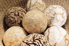 Bolas decorativas naturales en una cesta de madera Imagen de archivo