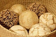 Bolas decorativas naturales en una cesta de madera Fotos de archivo