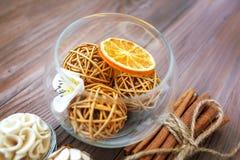 Bolas decorativas y naranja secada en la bola de cristal con canela en una tabla de madera con una variedad de artículos hermosos Fotografía de archivo libre de regalías