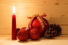 Bolas del Año Nuevo y conos rojos del pino con una vela roja ardiente en un fondo de madera Foto de archivo libre de regalías