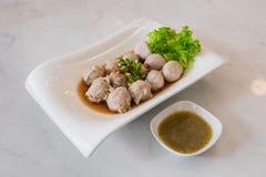 Bolas del cerdo con la inmersión picante en restaurante tailandés Fotos de archivo