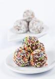 Bolas del chocolate con los desmoches coloridos en blanco Foto de archivo