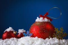 Bolas del concepto de la Feliz Navidad en la nieve, saludando Foto de archivo
