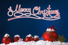Bolas del concepto de la Feliz Navidad en la nieve, saludando Fotografía de archivo