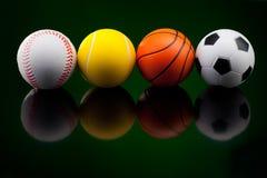 Bolas del deporte delante del fondo negro Foto de archivo libre de regalías
