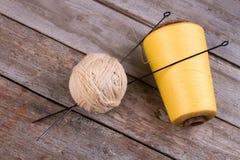 Bolas del hilado con las agujas que hacen punto en un fondo de madera Foto de archivo libre de regalías