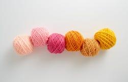 Bolas del hilo para obras de punto en tono rosado y amarillo Imagen de archivo