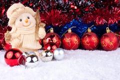 Bolas del muñeco de nieve y de la Navidad en nieve Imágenes de archivo libres de regalías