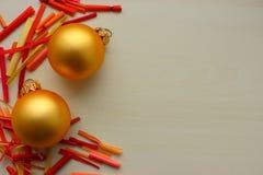 Bolas del oro como Año Nuevo y decoración de la Navidad con los palillos coloridos brillantes en el fondo blanco con el espacio d Imagenes de archivo