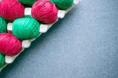 Bolas do colorido fio vermelho e verde em uma bandeja de papel do ovo Diagona imagens de stock