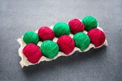 Bolas do colorido fio vermelho e verde em uma bandeja de papel do ovo skeins imagem de stock
