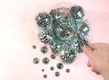 Bolas do disco para o partido da decoração que quebra-se em bolas pequenas em uma bacia com batedor de ovos à disposição no fundo fotos de stock royalty free