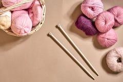 Bolas do fio Bolas do fio colorido em um prato de vime Fio para fazer malha em um fundo bege Confecção de malhas como um tipo de Fotografia de Stock