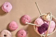Bolas do fio Bolas do fio colorido em um prato de vime Fio para fazer malha em um fundo bege Confecção de malhas como um tipo de Imagens de Stock