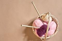 Bolas do fio Bolas do fio colorido em um prato de vime Fio para fazer malha em um fundo bege Confecção de malhas como um tipo de Foto de Stock Royalty Free