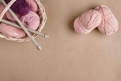 Bolas do fio Bolas do fio colorido em um prato de vime Fio para fazer malha em um fundo bege Confecção de malhas como um tipo de Imagem de Stock