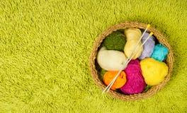 Bolas do fio para confecção de malhas, agulhas na cesta sobre a parte traseira verde do tapete Foto de Stock