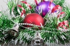 Bolas do Natal com festão verde e os sinos de prata Fotografia de Stock Royalty Free