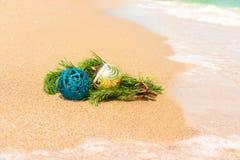 Bolas do Natal com o galho do abeto na areia Fotos de Stock