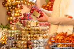 Bolas do Natal da compra do comprador em umas caixas plásticas Fotografia de Stock Royalty Free