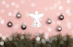 Bolas do Natal da pérola e figura do anjo no fundo cor-de-rosa com ramos de pinheiro imagem de stock
