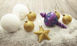 Bolas do Natal do ouro, bolas de neve, neve do inverno e estrela de brilho no fundo de madeira Fotografia de Stock Royalty Free