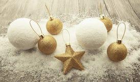 Bolas do Natal do ouro, bolas de neve, neve do inverno e estrela de brilho no fundo de madeira Imagens de Stock