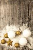 Bolas do Natal do ouro, bolas de neve, neve do inverno e estrela de brilho no fundo de madeira Fotografia de Stock