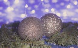 Bolas do Natal e ramos do abeto no fundo azul, conceito da iluminação da noite, fundo tonificado fotografia de stock royalty free
