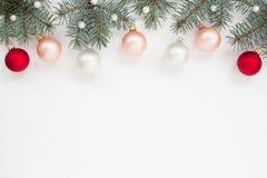 Bolas do Natal, grânulos, abeto vermelho na parte superior do textur de madeira branco Fotografia de Stock Royalty Free