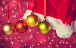 Bolas do Natal na fita com chapéu de Santa. Imagens de Stock Royalty Free