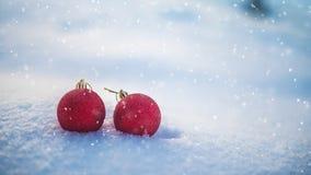 Bolas do Natal na neve e na queda de neve Imagens de Stock