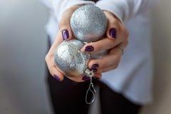 Bolas do Natal nas mãos Fotos de Stock