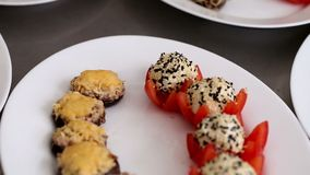 Bolas do queijo com as sementes e os cogumelos enchidos com o queijo apresentado em uma placa branca video estoque