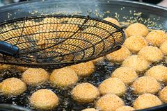 Bolas do sésamo que fritam no óleo quente imagens de stock