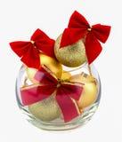 Bolas douradas do Natal e curva vermelha em um vaso de vidro Imagens de Stock Royalty Free
