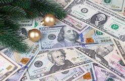Bolas douradas dos ramos de árvore do Natal no fundo do dinheiro foto de stock