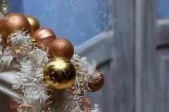 Bolas douradas marrons do Natal e decorações brancas da festão no fundo do ` s da porta Fotografia de Stock Royalty Free