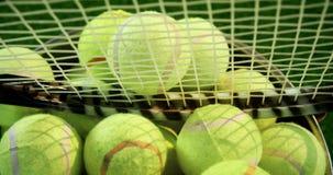 Bolas e raquete de tênis na cubeta no estúdio 4k vídeos de arquivo