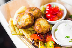 Bolas fritas de la patata en una placa Pequeñas bolas fritas de oro hechas de las semillas de los purés de patata, de los huevos, Foto de archivo libre de regalías