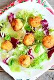 Bolas fritas de la patata, mezcla de la ensalada, albahaca en una placa Bolas fritas deliciosas del puré de patata con las semill Fotografía de archivo