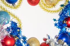 Bolas multicoloras de la Navidad con malla en un fondo blanco Fotografía de archivo