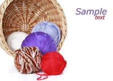 Bolas multicoloras del hilado en cesta de mimbre Foto de archivo