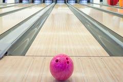 Bolas na pista de boliches contra dez pinos Foto de Stock