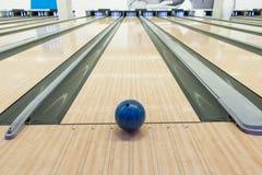Bolas na pista de boliches contra dez pinos Fotografia de Stock