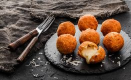 Bolas o croquetas fritas del queso de la patata con las especias en la placa negra sobre fondo de piedra oscuro fotografía de archivo libre de regalías